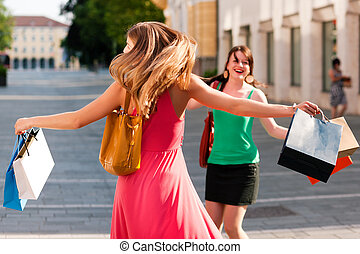 women downtown shopping with bags - Two women being friends...