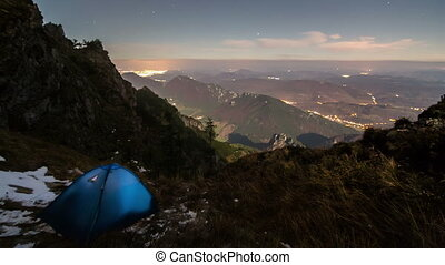 Camping in mountains under night sky with moonlight time lapse