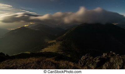 Fast moving night clouds in mountain time lapse