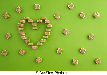 Sugar cubes shaped as heart on greenery background. Top...