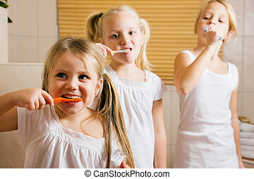 Children brushing teeth - Three children - sisters -...