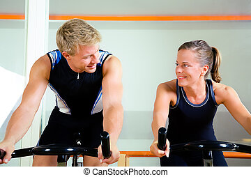 Spinning in the gym - Couple using bikes in a club, looking...