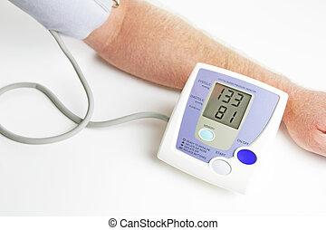 Blood pressure monitoring - Man measuring his own blood...