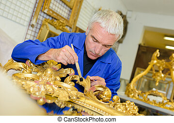 Man renovating picture frame with gold leaf
