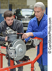 teacher and student in auto mechanics training class