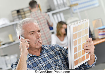 Man on telephone with skeptical expression, holding color...