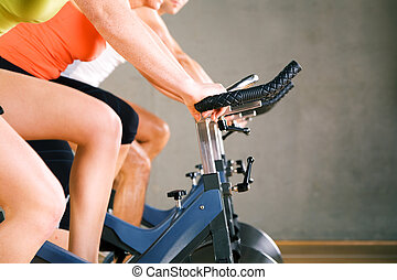 Bicycle Spinning in gym - Three people spinning in the gym