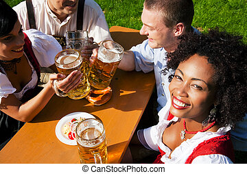Group of four friends in beer garden eating and drinking -...
