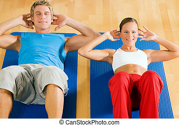 Couple doing Sit-ups - Couple with brightly colored clothes...
