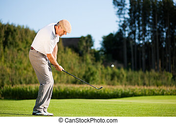 Senior golf player in summer - Senior golfer doing a golf...