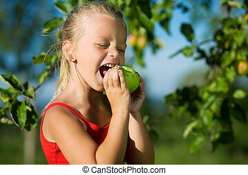 Nibble of a sweet apple - Little girl nibbling a sweet apple