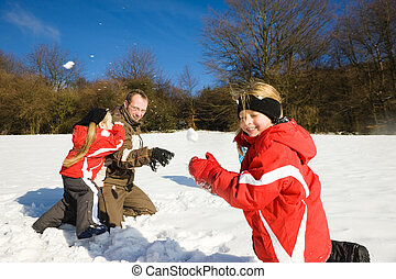 Family having a snowball fight - Family with kids having a...