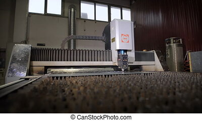 Industrial laser cutter with sparks. The programmed robot head cuts with the aid of a huge sheet of metal temperature. Modern machine improves quality and productivity.