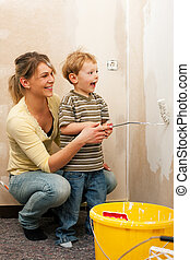 Family painting wall of new home - Family - mother with son...