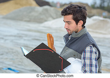Man on construction site holding file and baguette