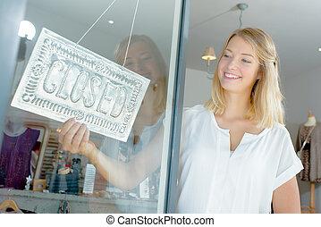woman closing a shop