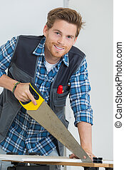 portrait of carpenter working with a saw at construction site