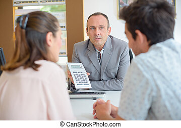 Salesman holding calculator screen towards couple