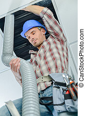 worker doing the ventilation system