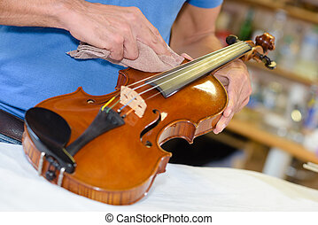 Man polishing violin with cloth