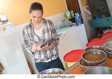 pretty woman preparing bowls of dog food at animal shelter
