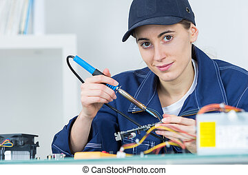 Female technician using soldering iron