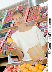 Lady in greengrocers holding paper bag and an orange