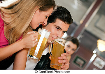 Couple in bar drinking beer flirting - Group of people in a...
