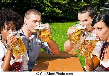 Group of four friends in beer garden - Group of four people...
