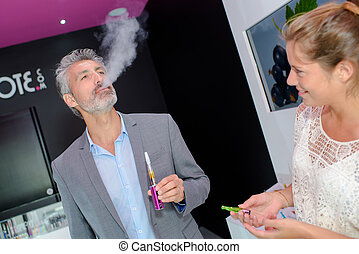Man trying an electronic cigarette, breathing out vapour