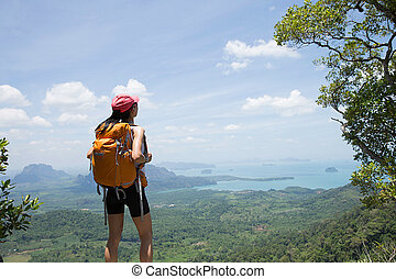 young traveler with backpack standing on the mountain peak...
