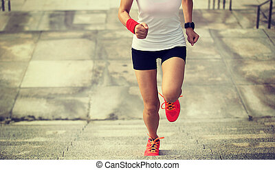 young fitness woman running upstairs on city stairs