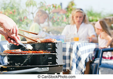 Family having a barbecue in the garden - focus on cooking in...