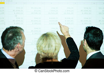 Discussing the spreadsheet - Group of people in front of a...