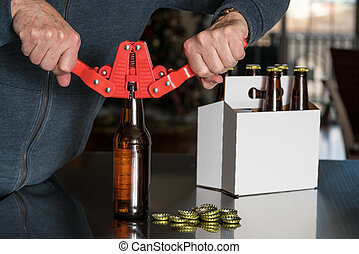Man using capper to put metal caps on beer bottle - Brewer...