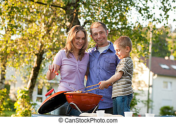 Family having barbecue in front ofhome - Family - father and...