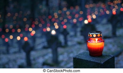 Cemetery at night with colorful candles for All Saints Day. All Saints' Day is a solemnity celebrated on 1 November by the Catholic Church. Static shot.