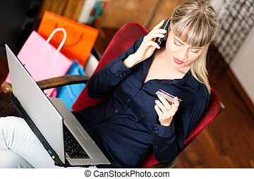 woman shopping online via Internet from home - Woman sitting...