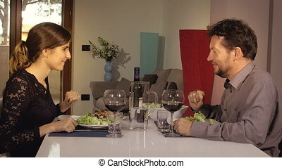 Couple in love holding hands during romantic dinner at home