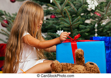 Child opening Christmas presents - Cute Child with teddy...