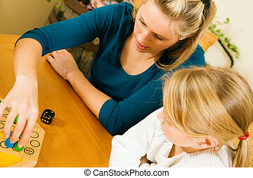 Mother and child playing board game