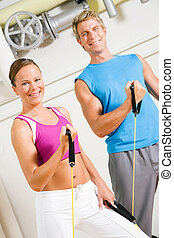 Couple doing Tube Training in gym - Very fit couple in a gym...