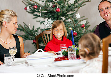 Family having Christmas Dinner - Family eating a traditional...