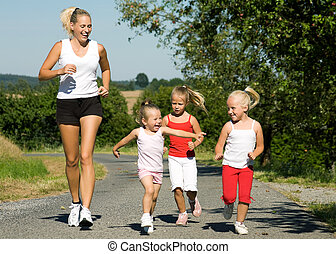 Jogging with the family - young mother jogging with her...