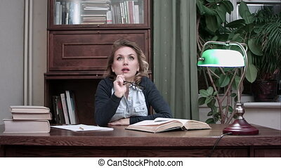 Serious woman thinking sittnig at work desk with books -...