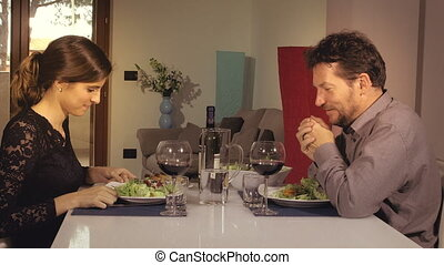 Happy couple toasting with wine during romantic dinner at...