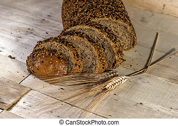 Fresh bread slice with sunflower seeds on wooden table and...