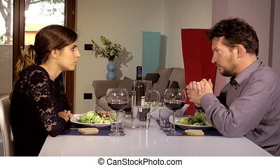 Man talking to wife about serious problem during lunch at...