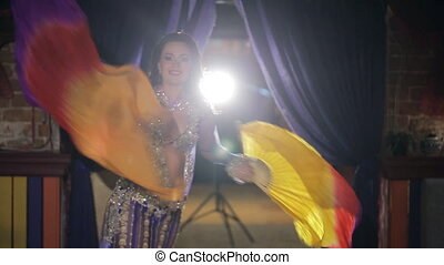 Belly Dancer with two colored veils waving at the concert in a cafe.