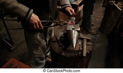 Blacksmith forges the horseshoe